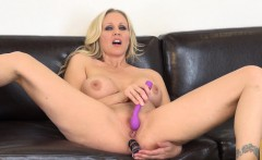 Busty Julia Ann spreads her long legs and sticks a dildo in each hole